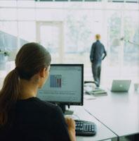パソコンの前の外国人女性後姿と窓辺の男性後姿