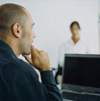 オフィスの外国人女性とパソコンの前で頬杖をつく男性