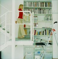 本棚のそばの階段を下りる外国人女性