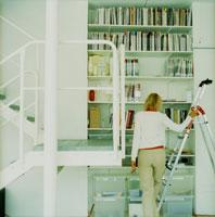 本棚の前に立つ外国人女性後姿