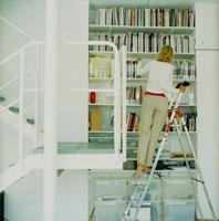 本棚の本を探す外国人女性後姿