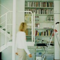 本棚の前を歩く外国人女性