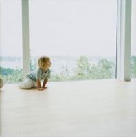 窓辺の床に座って手をつく外国人女の子