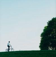 草原で自転車に乗る外国人男性と空