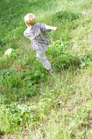 草原でボール遊びをする外国人男の子後姿