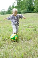 草原でボール遊びをする外国人男の子