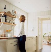 キッチンで棚に手を伸ばす女性