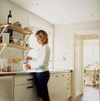 キッチンでコーヒーを入れる女性