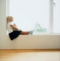 窓辺に座るぬいぐるみを持った女の子