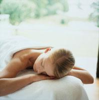 エステのベッドでリラックスする女性