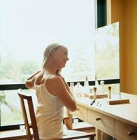 ドレッサーの前で髪をアレンジする女性