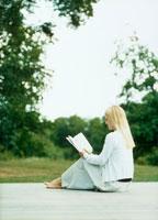 テラスに座り本を読む女性