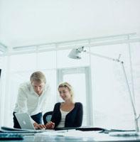 オフィスでパソコンを見る男女