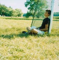 サッカーゴールに寄りかかる男性
