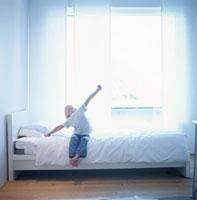 ベッドに座って伸びをする外国人女の子