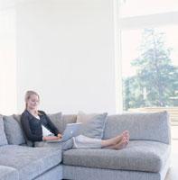 ソファに座りノートパソコンを見る外国人女性