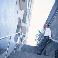 階段で携帯電話を使う外国人男性