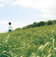草原と空とブルーのスカートの女性