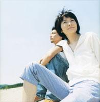座るカップルと青空