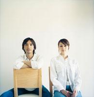 室内の白い壁の前でイスに座るカップル