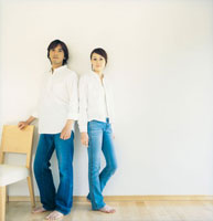 室内の白い壁の前に立つカップル