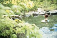 新緑の露天風呂の女性後姿