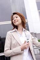 携帯を持つ笑顔のビジネス女性