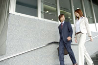 階段を下りるビジネスカップル