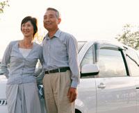 車の前に立つ中高年夫婦