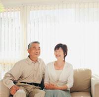 ソファに座る中高年夫婦