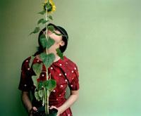 ヒマワリの鉢植えを持つ女の子