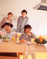 ダイニングで食事をする姉弟とキッチンの両親