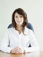 イスに座り正面を見るビジネス女性