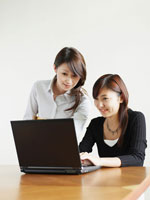一緒にパソコンをする女性2人