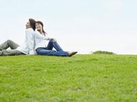 芝生に座るカップルと大空