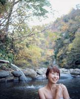 紅葉の露天風呂と笑顔の女性