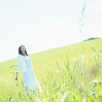 緑の草原に立つ白い服の女性