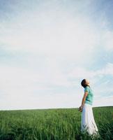 緑の草原に立つ女性と青空