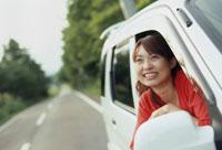 車の窓から外をながめる笑顔の女性
