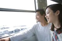 列車の車窓から外を眺めるカップル