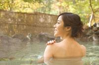 紅葉と露天風呂に入る女性