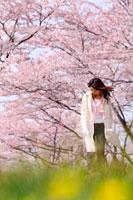 桜と白いコートを着た女性