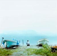 湖と2艘のボートと男性の後姿