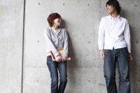 壁の前に立つ学生カップル