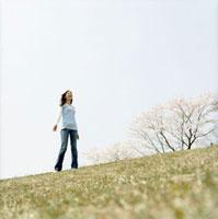青空の桜咲く草原に立つ女性