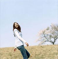 青空の桜咲く草原で振り向く女性
