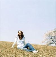青空の桜咲く草原に座る女性