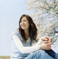 青空の桜咲く草原に座る女性上半身