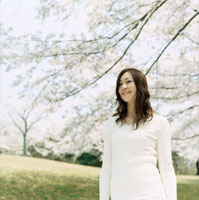 桜咲く草原に立つ女性ポートレート