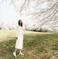 桜咲く草原に立つ女性